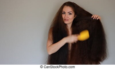 Beautiful young woman combing comb very thick and long hair....