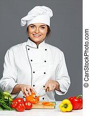 Beautiful young woman cook cutting fresh paprika