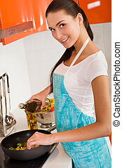 Beautiful young woman cooking in the kitchen