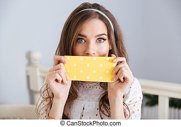 Beautiful young woman covered her face with napkin in cafe