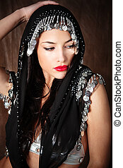 woman covered with black scarf holding hand on her head