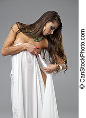 Beautiful young woman covered with white sheet
