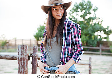 Beautiful young woman cowgirl in hat standing on ranch -...