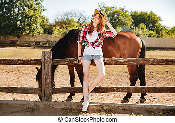 Beautiful young woman cowgirl staning with her horse on...