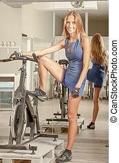 Beautiful Young Woman Cycling Gym