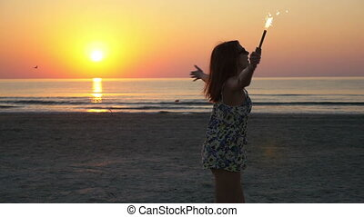 Beautiful young woman dancing on a sandy beach holding a firework candle in her hand