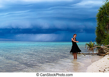 Beautiful young woman dancing on the beach with a tropical storm