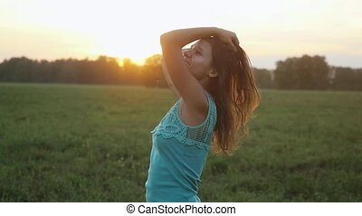 Beautiful young woman dancing outdoors on a sunset with sun shining bright through the sun in slow motion.