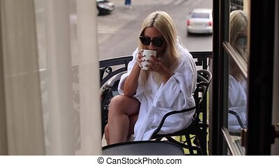 Beautiful young woman daydreaming with a cup of hot coffee on the balcony
