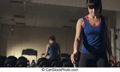 Beautiful young woman doing abdominal exercises on Roman chair in the gym in front of mirror
