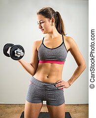 Beautiful young woman doing dumbbell curl