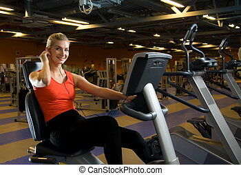 Beautiful young woman doing exercise in a gym while listening to music