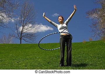 hula hoop - Beautiful young woman doing hula hoop outdoors ...