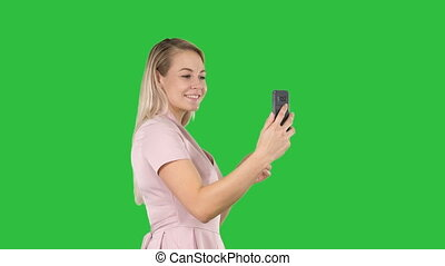 Beautiful young woman doing selfies on a Green Screen, Chroma Key.