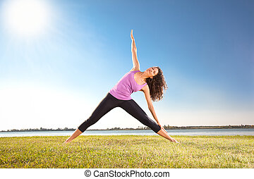 Beautiful young woman doing yoga exercise on green grass
