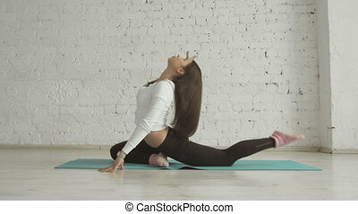 Beautiful Young Woman Doing Yoga Exercise One-Legged King Pigeon Pose, Side View