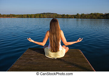 Beautiful young woman doing yoga exercise outdoors