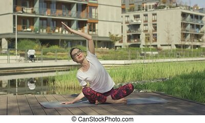 Beautiful young woman doing yoga outdoors near home - Young...