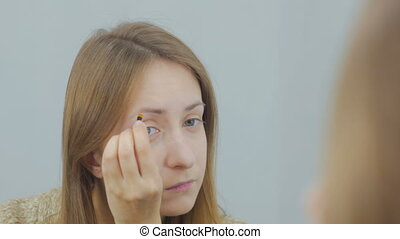 Beautiful young woman drawing eyebrows in white room