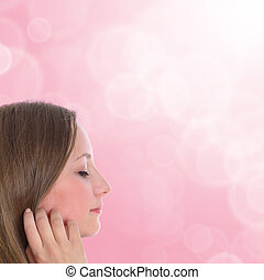 Beautiful young woman dreams - on soft pink blurred background