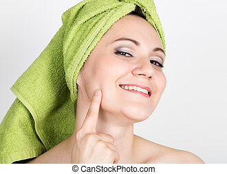 beautiful Young woman dressed in a bath towel makes a cosmetic mask on the face. beauty industry and home skin care concept