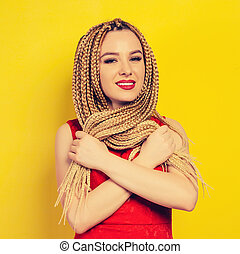 beautiful young woman dressed in a red dress, crossed arms holds pigtails. studio
