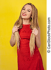beautiful young woman dressed in a red dress, holds pigtails.