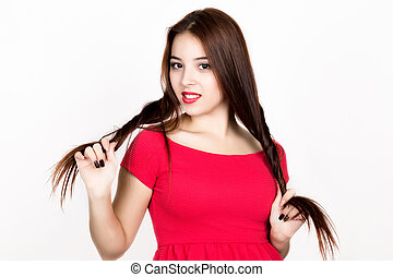 beautiful young woman dressed in a red dress, holds pigtails. studio shot