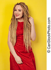 beautiful young woman dressed in a red dress, touches African pigtails.