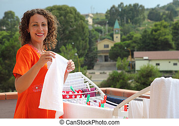 beautiful young woman dressed in red dress hangs clean wear on balcony. in background of Italian church
