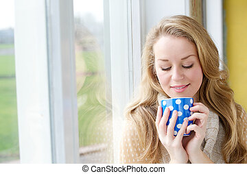 Beautiful young woman drinking a cup of tea