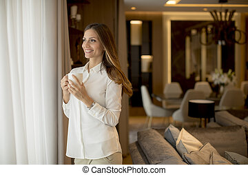 Beautiful young woman drinking coffee and looking through window while standing in the apartment