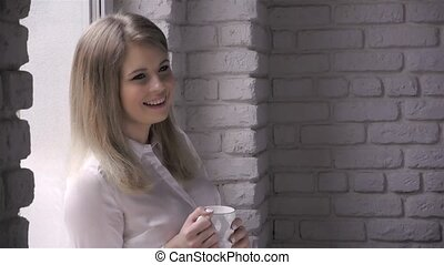 beautiful young woman drinking coffee and smiling