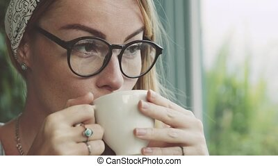 Beautiful young woman drinking coffee in cafe. Girl dreaming. Female wearing glasses.