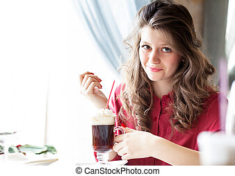 Beautiful young woman drinking coffee latte in a cafe
