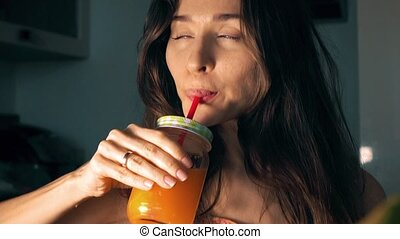 Beautiful young woman drinking fresh orange juice at home. 4K video