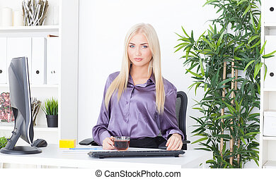 Beautiful Young Woman drinking hot tea at office