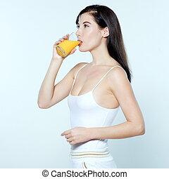 beautiful young woman drinking orange juice on studio white isolated background