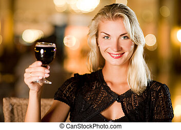 Beautiful young woman drinking red wine in a restaurant
