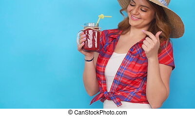 Beautiful young woman drinking strawberry smoothie on blue background