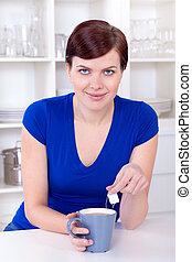 beautiful young woman drinking tea at home