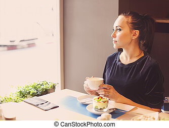 Beautiful young woman drinking tea in cafe