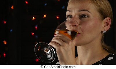 Beautiful young woman drinking white wine in a dark. beauty lady with glass of wine. 4K