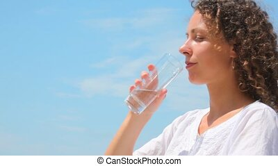beautiful young woman drinks water from glass, blue sky in background