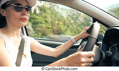 Beautiful young woman driving a car in Mediterranean scenery
