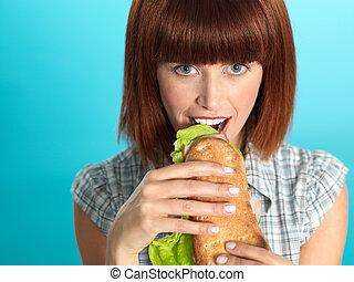 beautiful young woman eating a big sandwich