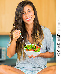 Beautiful young woman eating a bowl of healthy organic salad