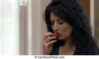 Beautiful young woman eating a strawberry enjoying a healthy lifestyle