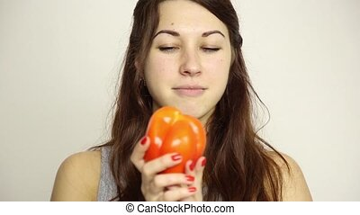beautiful young woman eating an vegetables. holding a red pepper. healthy food - healthy body concept
