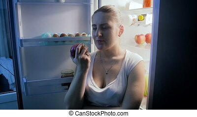 Beautiful young woman eating fresh apple on kitchen at night...